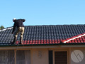 A friendly staff member professionally coating a roof during one of our Melbourne roof repairs