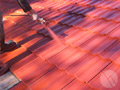Coating a repaired roof with our 3-coat sealing system, which includes primer, sealer and topcoat